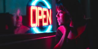 "Women sitting next to neon ""open"" light"